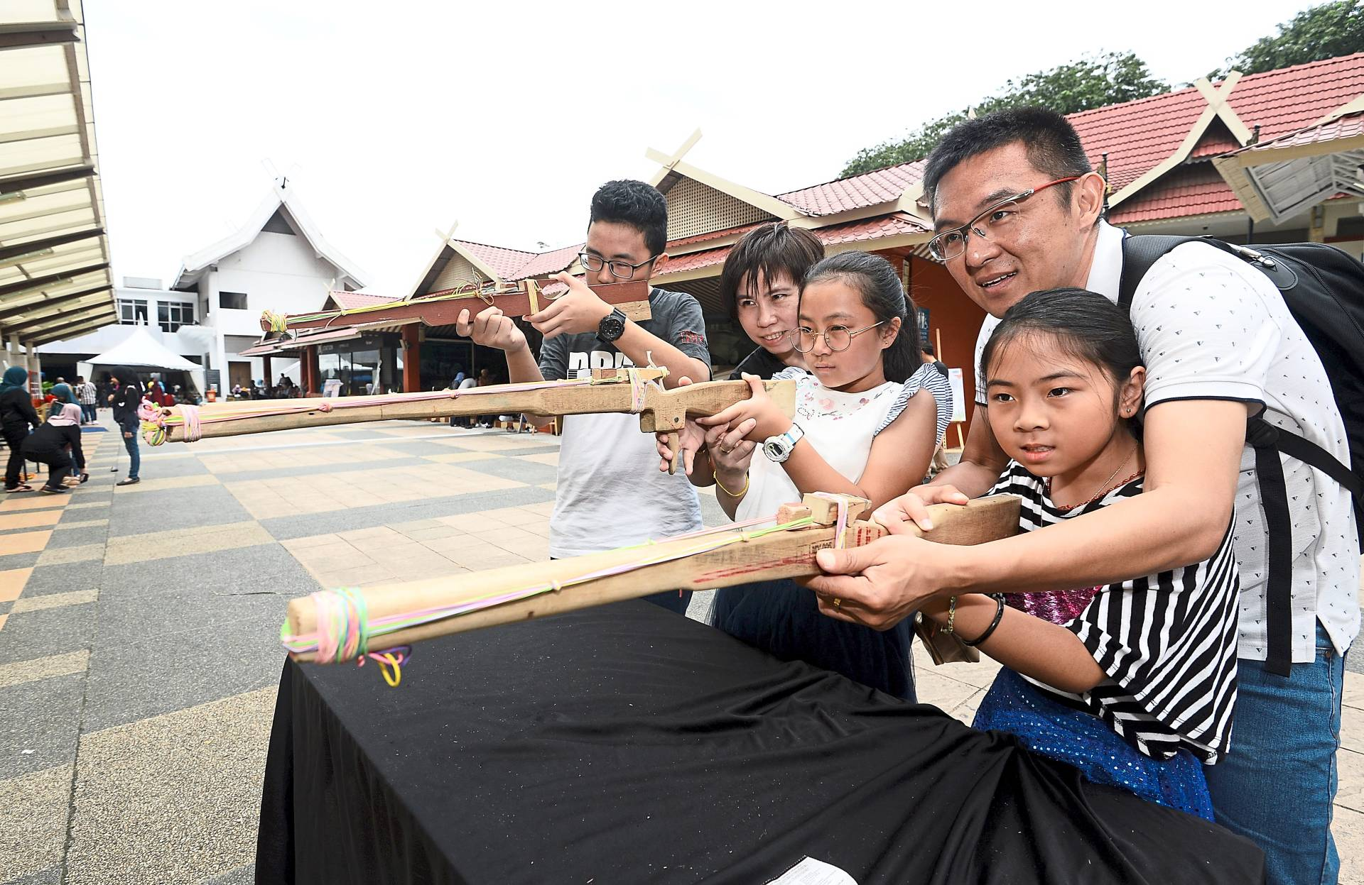Choy (in white shirt, right, 2nd row) and his wife Lee Mei Tin (2nd from left, 2nd row) showing their kids (from left, first row) Choy Min Han, Choy Qin Lin and Chon Qin Ru how to aim using a senapang kayu at the Muzium Negara's Nostalgia Anak Kampung programme.-  AZHAR MAHFOF/The Star