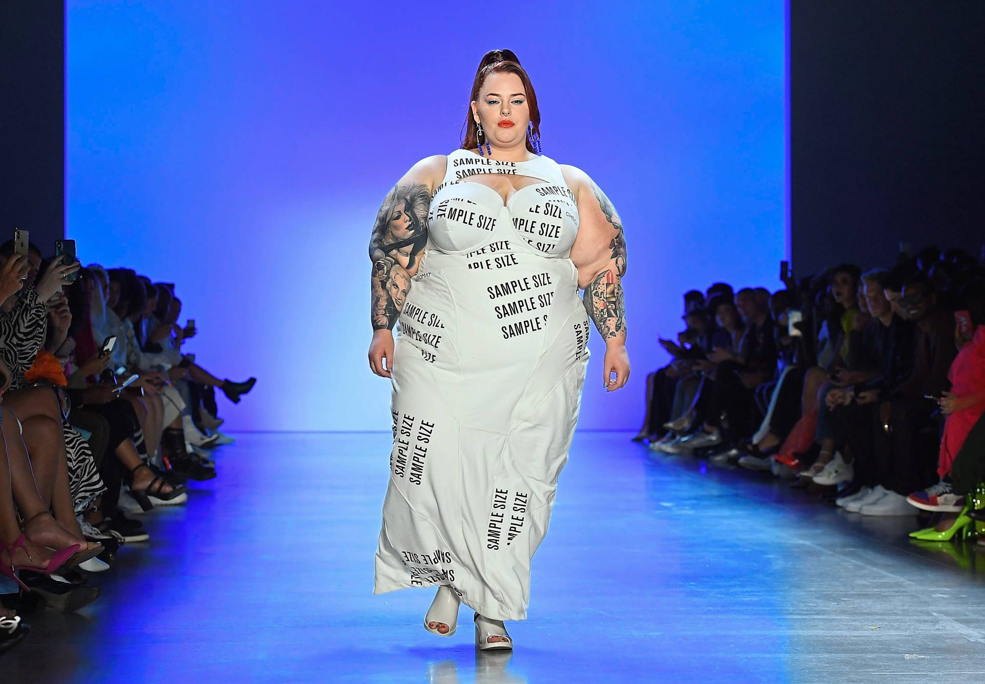 "Plus-size model Tess Holiday walking the Chromat Spring/Summer 2020 runway. The dress was emblazoned with the phrase ""sample size"", a term that refers to the standardised proportions fashion designers use to make women's clothing."