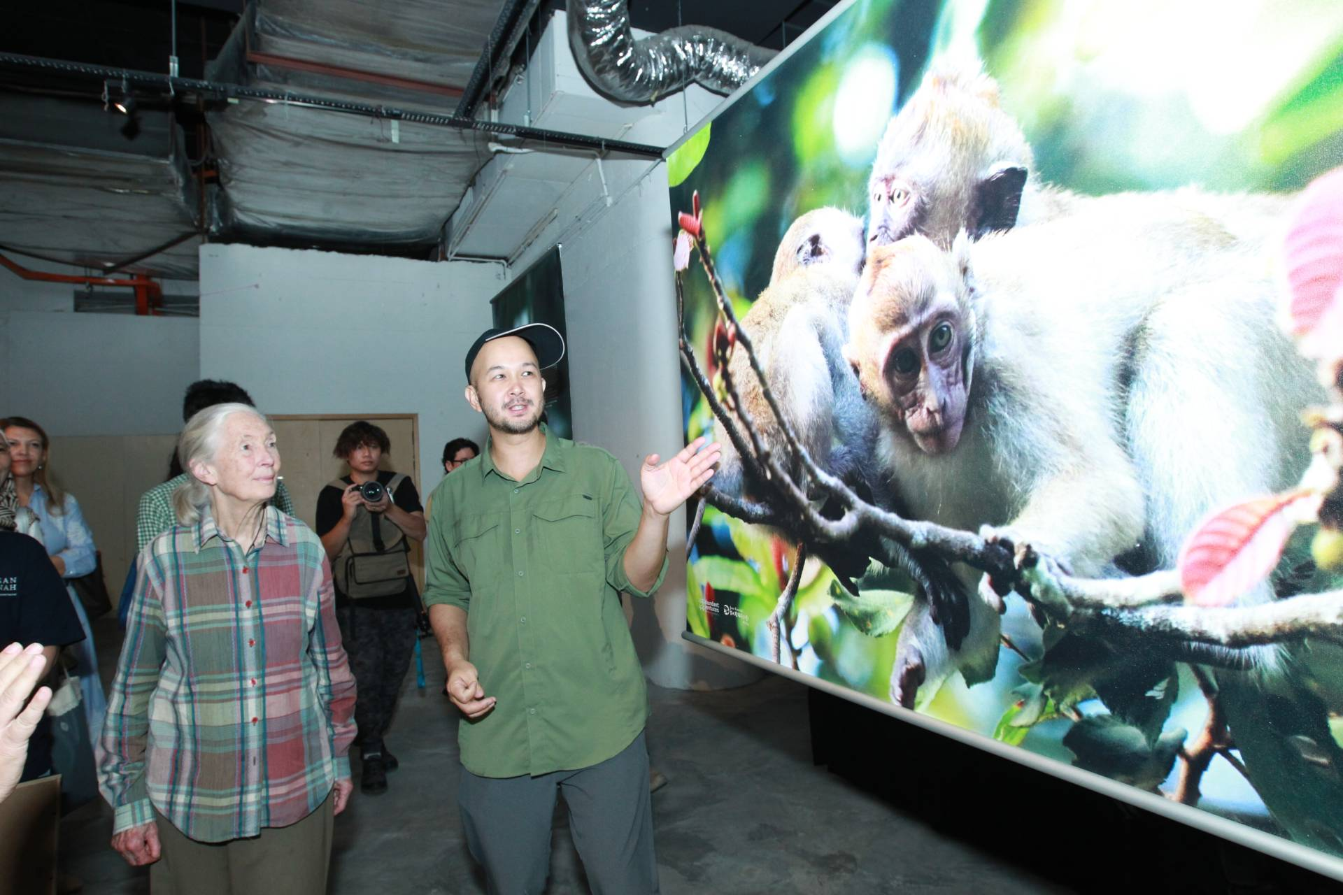 Photographer Peter Ong (right) shows Goodall one of his photographs in Project Monyet.
