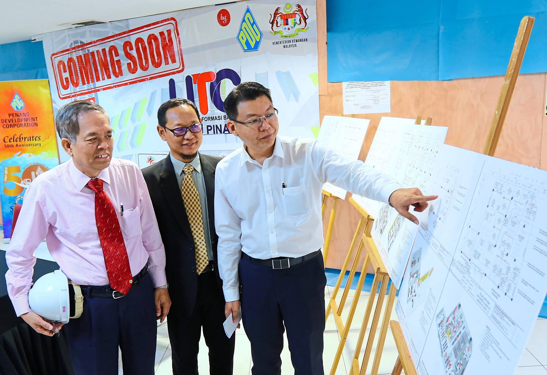(from left) Ang,  Aziz and  Teh discussing the layout plan on display during their working visit to the site of the Komtar UTC.