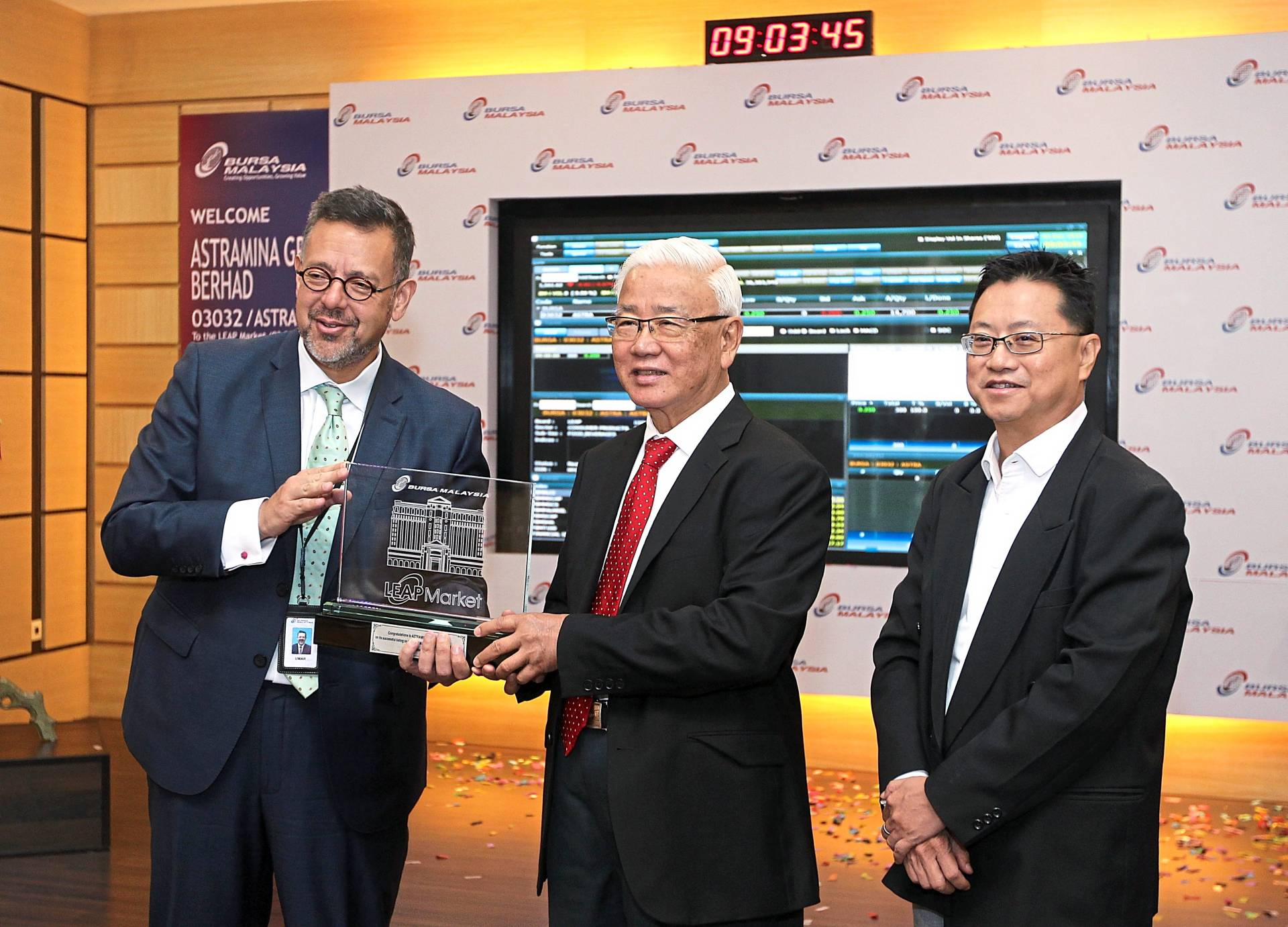 Good taste: Astramina Group non-independent non-executive chairman Tan Sri Wong See Wah (centre) receiving a plaque from Bursa Malaysia CEO Datuk Muhamad Umar Swift after the listing ceremony. Looking on is Foo.
