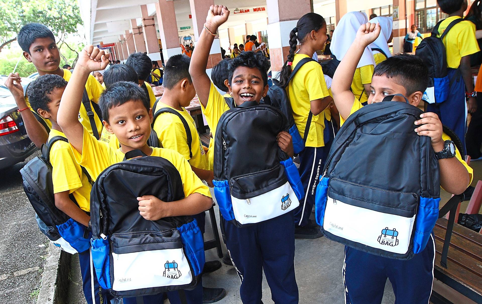 Pupils of SK Padang Tembak are all smiles after receiving school necessities from CapitaLand.