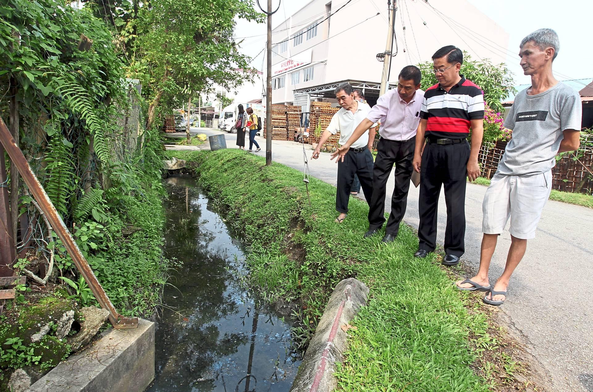 (From right) Ng, Wong, Tho and Yee showing the clogged drain along Jalan Jambu Air Laut.