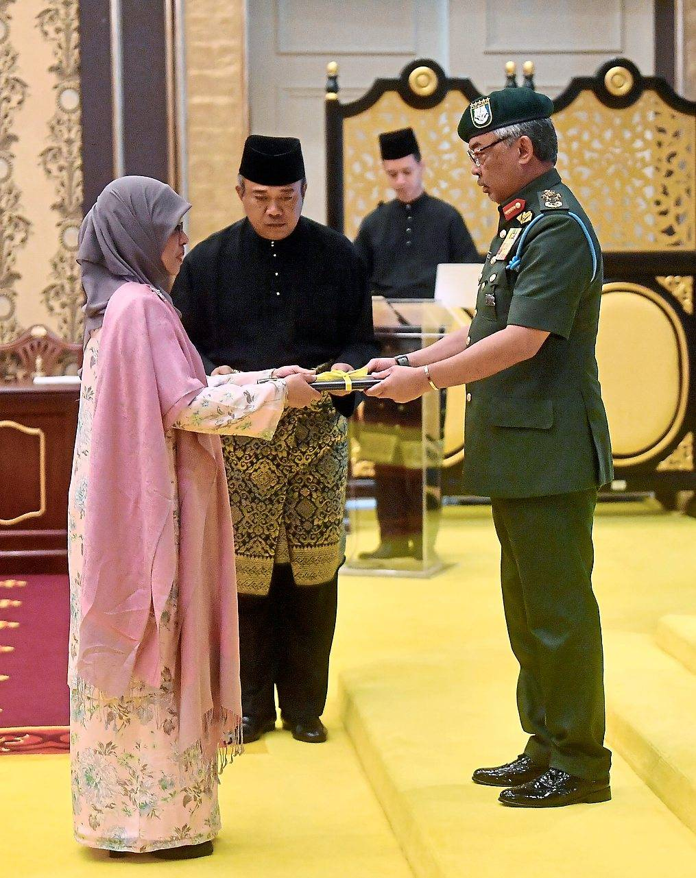 Official promotion: Sultan Abdullah presenting the letter of appointment to Hadhariah. — Bernama