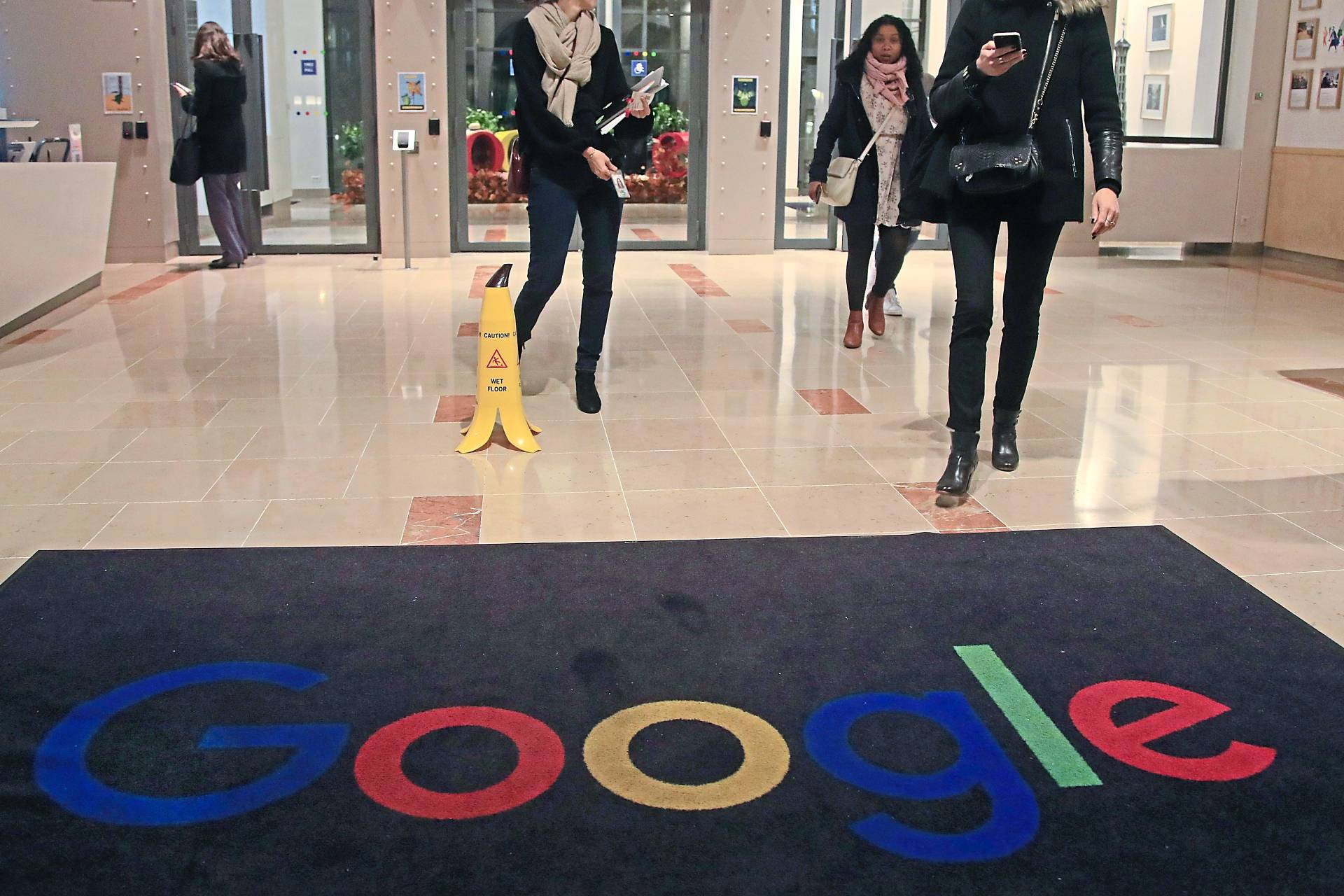 A file photo of Google employees walking out of the entrance hall of Google France in Paris, where the government is moving to tax digital services. In Malaysia, Google is preparing to deal with digital taxes too. — AP