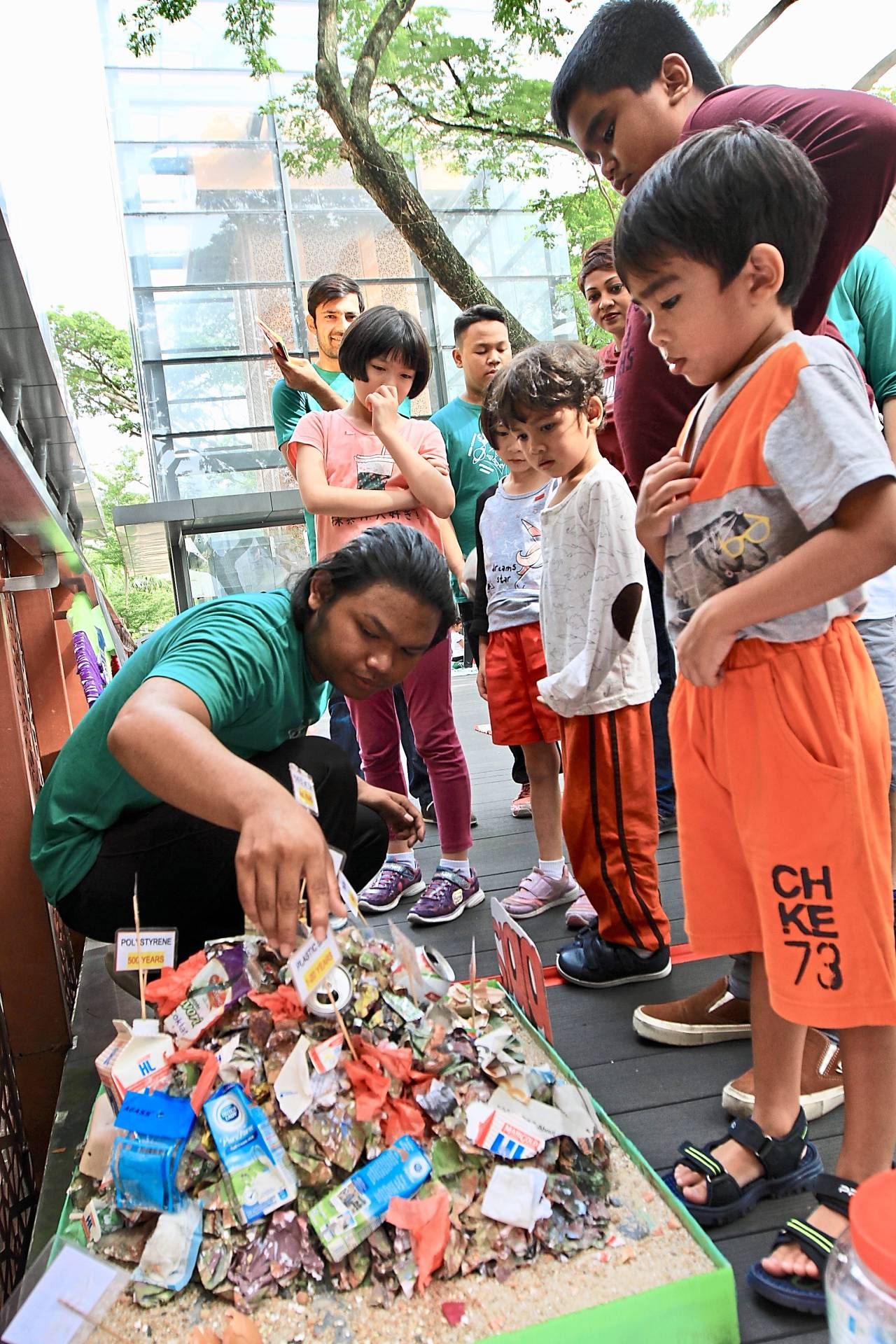Muhammad Hafiz, 19, engaging with children at the exhibition of recycled products during the River of Life Public Outreach Programme Phase 5 in Kuala Lumpur.