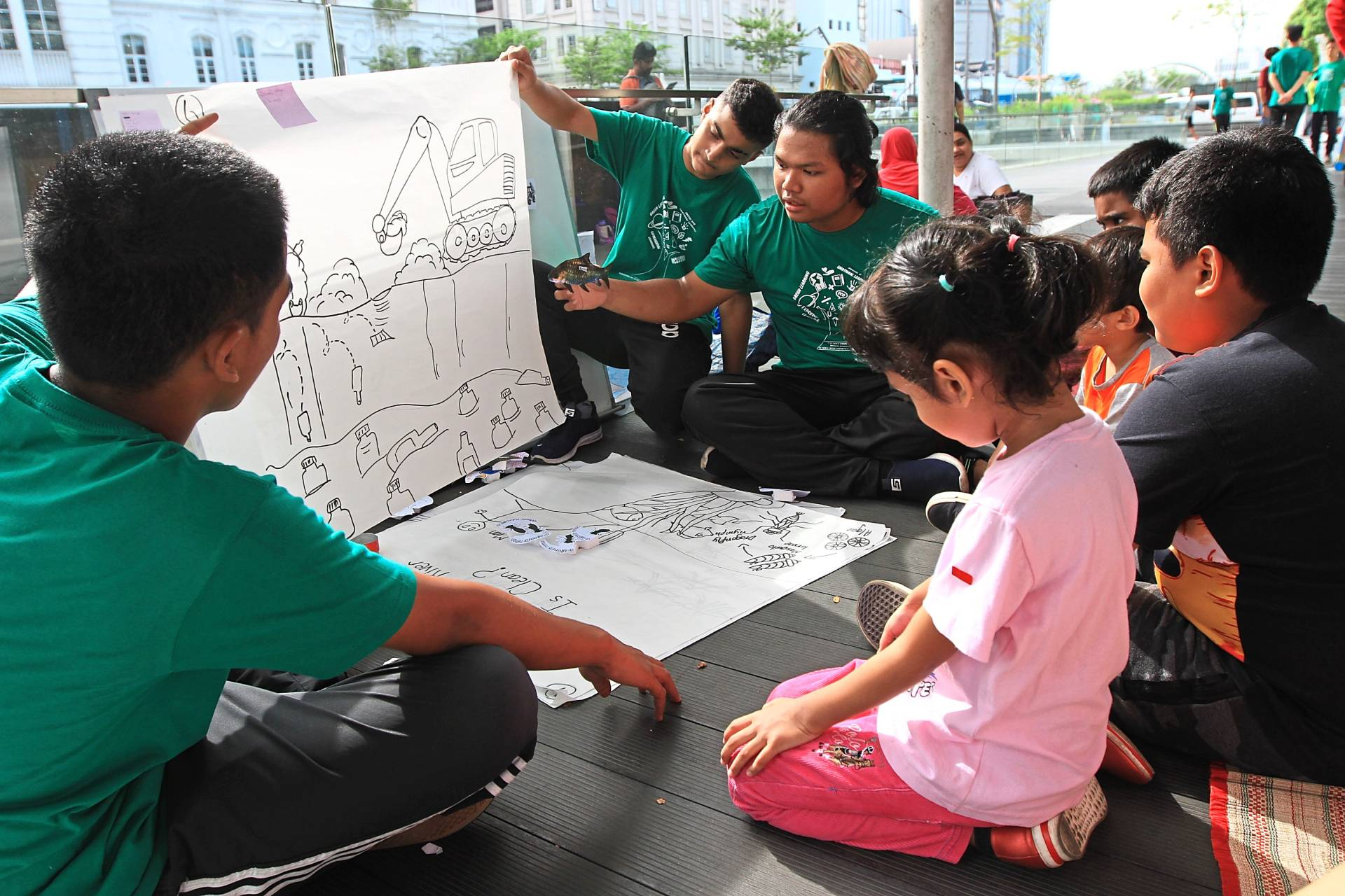 Yayasan Chow Kit youths (in green T-shirt) keep the children entertained during a storytelling session.