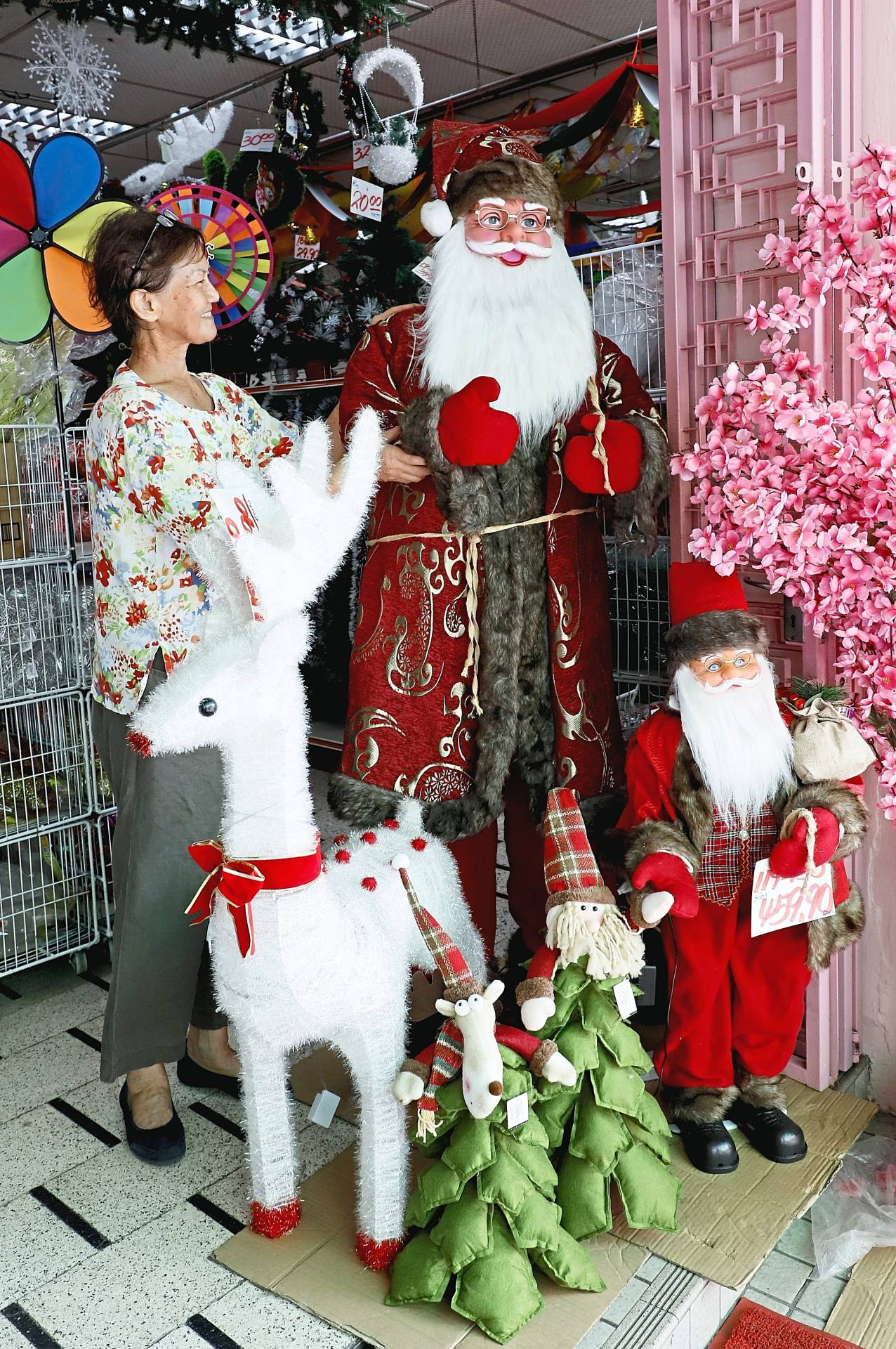 Lu making sure Santa Claus looks presentable at the entrance of her shop in Jalan Dr Lim Chwee Leong, George Town, Penang. — Photos: LIM BENG TATT/The Star