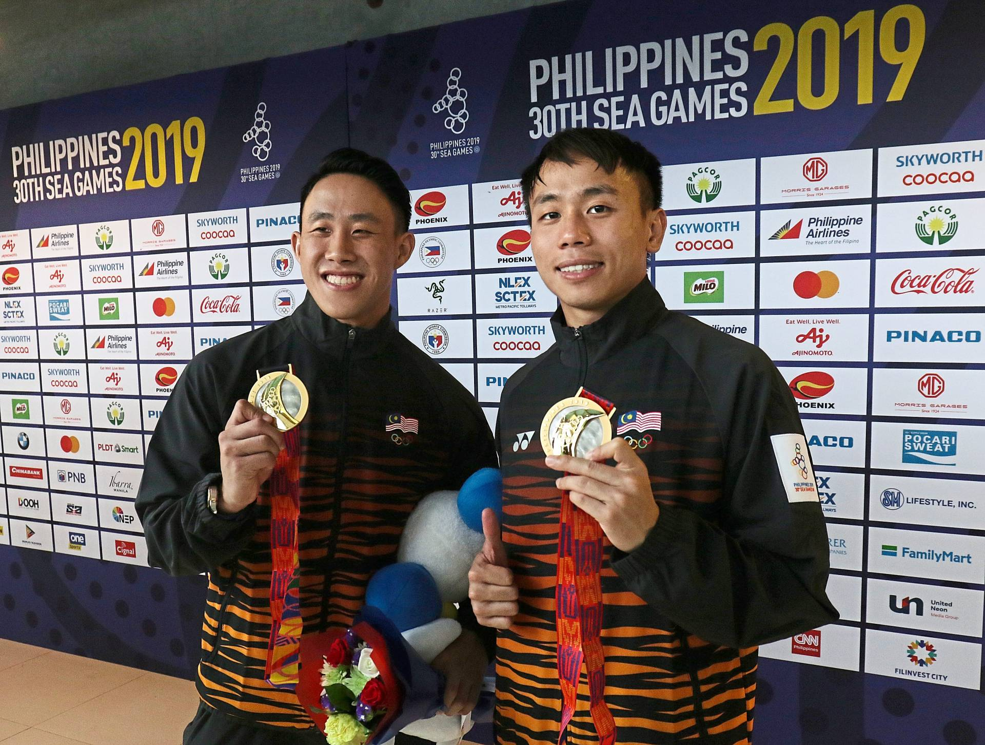 Ooi Tze Liang (left) and Chew Yiwei posing with their 3m synchronized springboard gold medals.