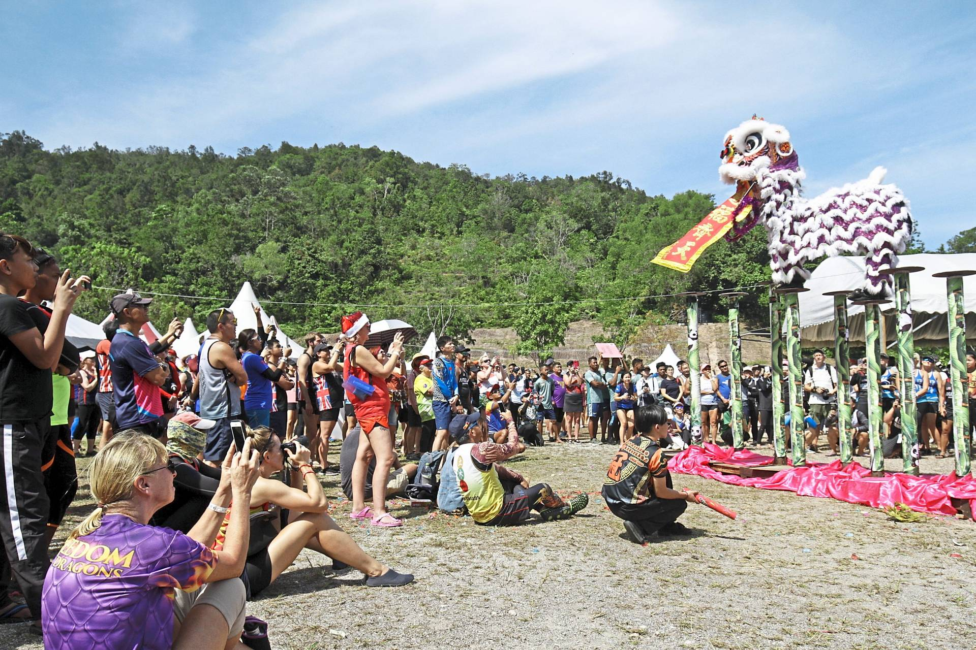 The crowd being entertained by a lion dance performance on stilts.