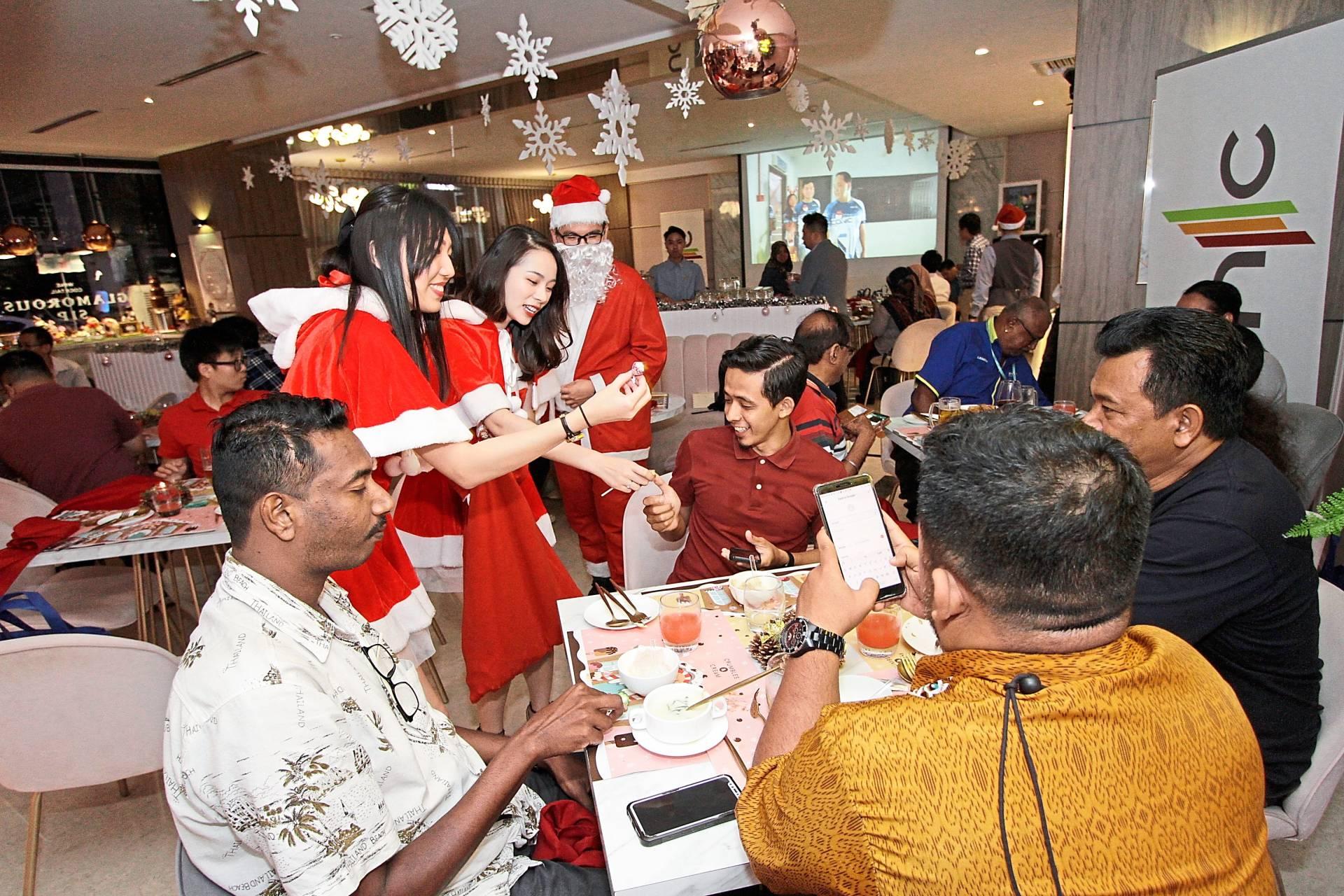 Santa Claus and Santarina giving sweets to pressmen.