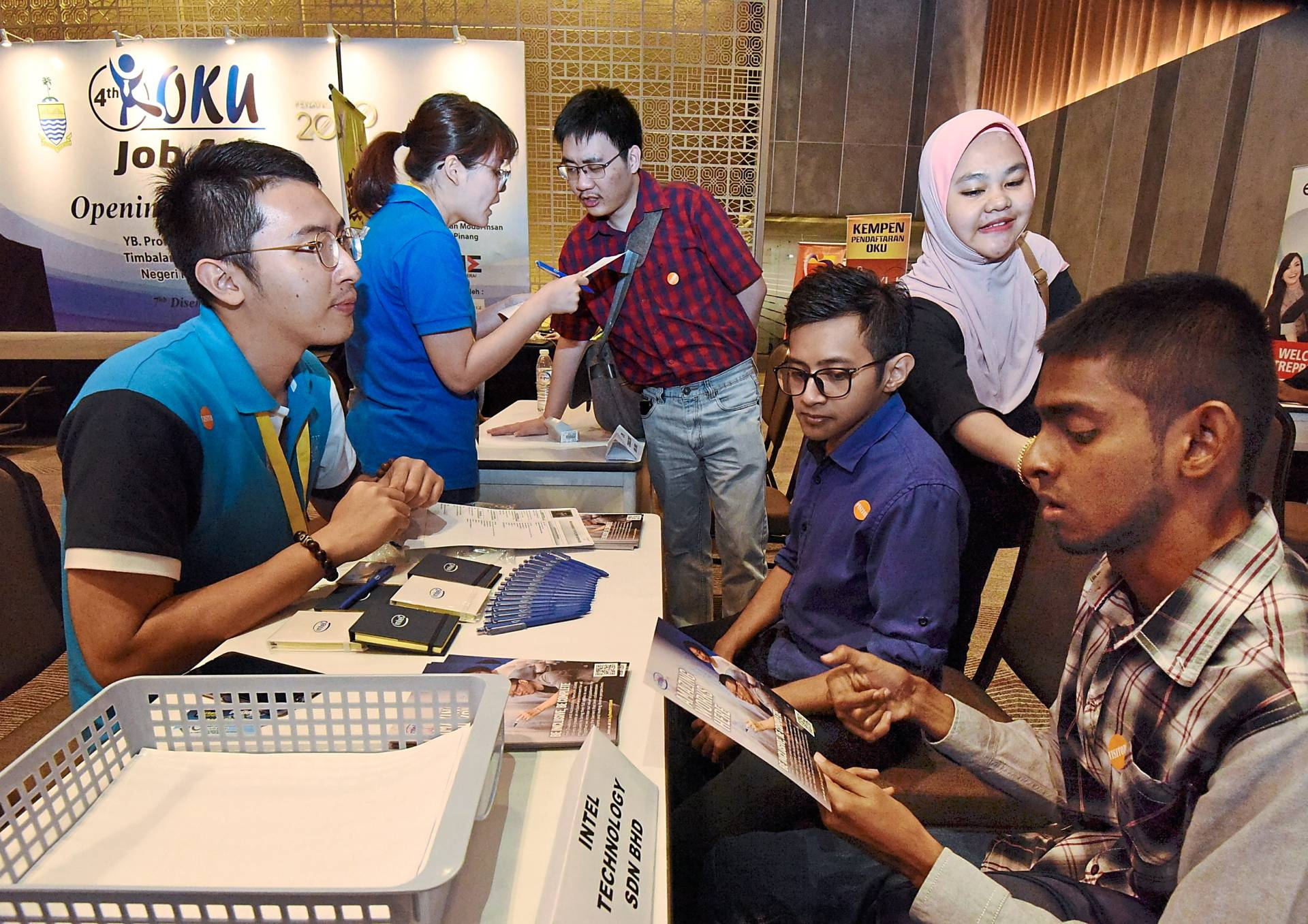(From right) Muhammad Syafiq Ameen, Muhammad Syafiq Norhasdi and Suziela (standing) checking out jobs at the Intel booth attended by HR campus programme manager Alex Goon (left).