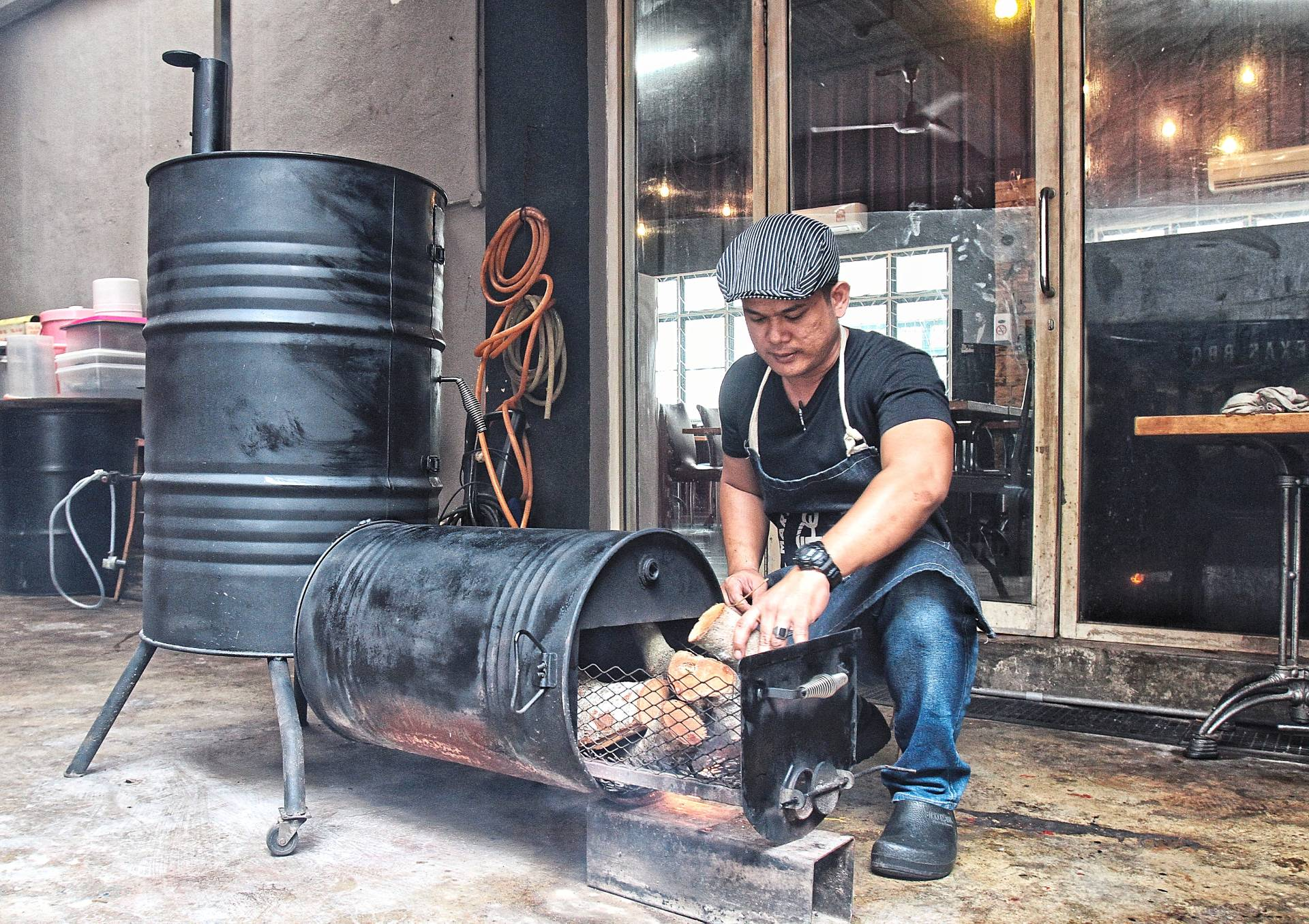 Arizal fashioned his smoker himself with recycled materials and uses local wood to fuel it.