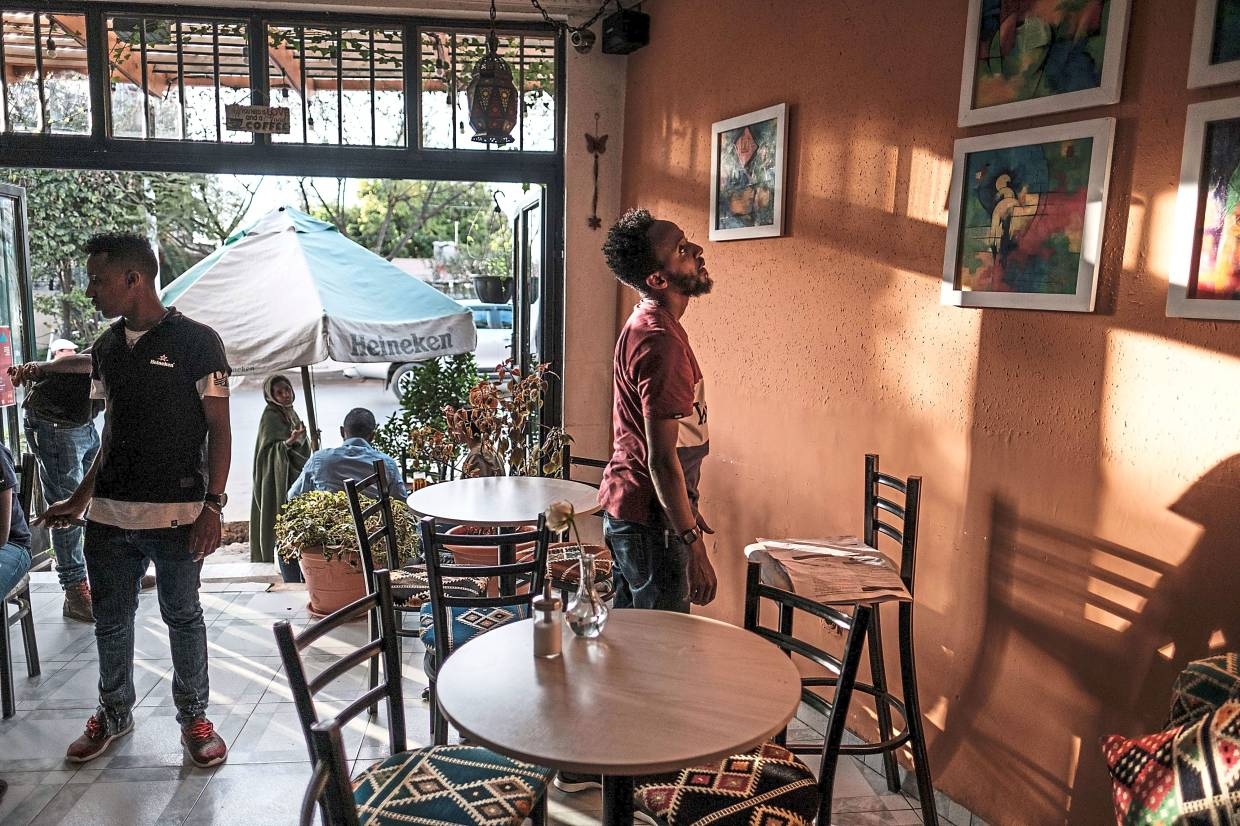 Mulubrhan (right) views his framed paintings with a staff of a coffee shop in Addis Ababa as he prepares an exhibition there.