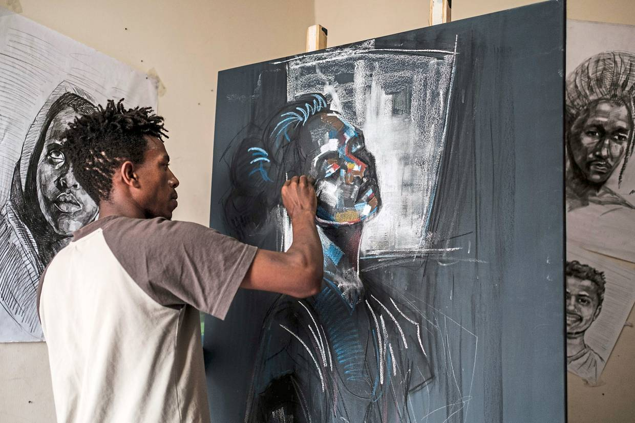 Eritrean artist Nebay, 23, is pictured while working on a painting in his room and studio in Addis Ababa.