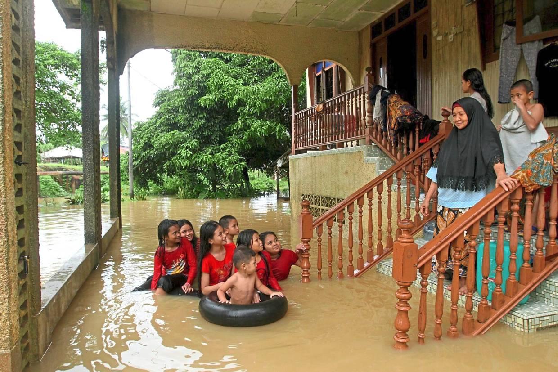 Azizah Said, 76, watching her kids playing in floodwaters outside her home in Kg Keroh, Kuala Krai.