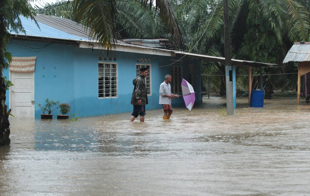 Kampung Belukar Durian villagers Abuddin Hassan(right) and Kasman Jamal preparing themselves to face the flood at Kota Tinggi. More than 9,000 people in Johor have been forced to evacuate to 93 temporary evacuation centres (PPS) in nine districts across the state after their homes were hits by floods following continuous heavy rainfall. NUR AISYAH MAZALAN/The Star