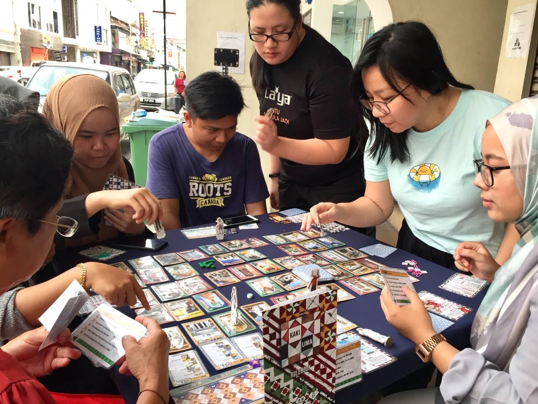 Players on a kaki lima along Lebuh Pantai in George Town playing the board game. Photo: Kaki Lima