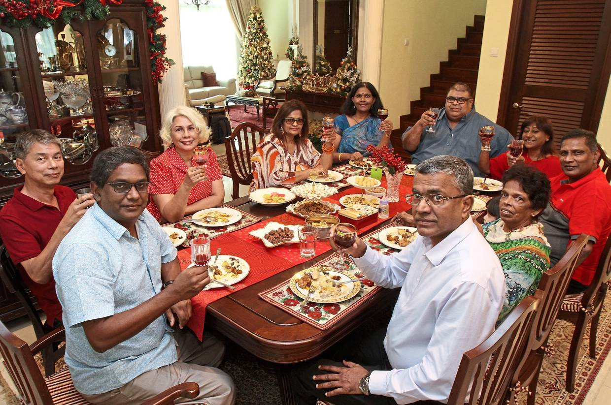 Juanita (in blue) and her husband Michael (foreground, in light blue shirt) always invite family and friends over, in batches, for Christmas.