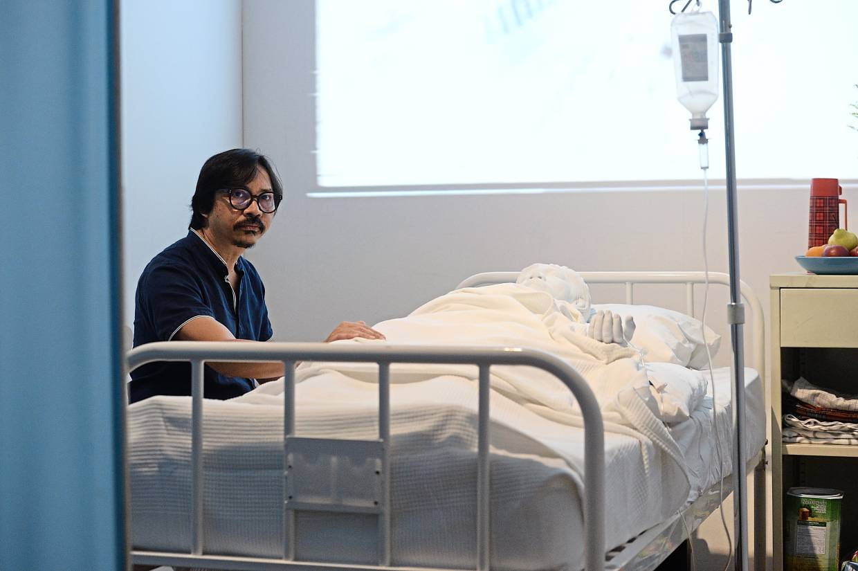 Ahmad Fuad poses with his installation project 'Mat Jenin Is (Always And Always Will Be) Dreaming To Death' (fibreglass cast, hospital bed, intravenous drip, single-channel video with sound, side table, chair, wilted flowers, bowl of fruit, 1998, recreated in 2019). Photo: The Star/Ong Soon Hin