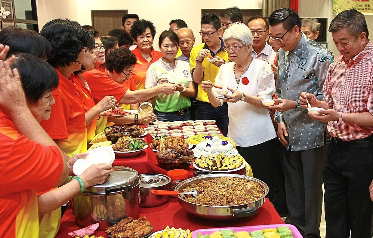 Chong Eng (in white) being served tang yuan and an array of local delicacies after launching the celebration at the Seberang Prai Hokkien Association hall in Bukit Mertajam. —Photos: ZHAFARAN NASIB/The Star