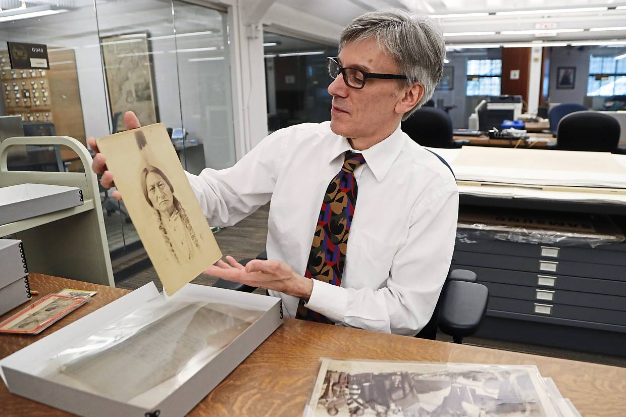 Lewis shows a photograph of Sitting Bull from the photographic collection acquired by the library in 2016. - AP