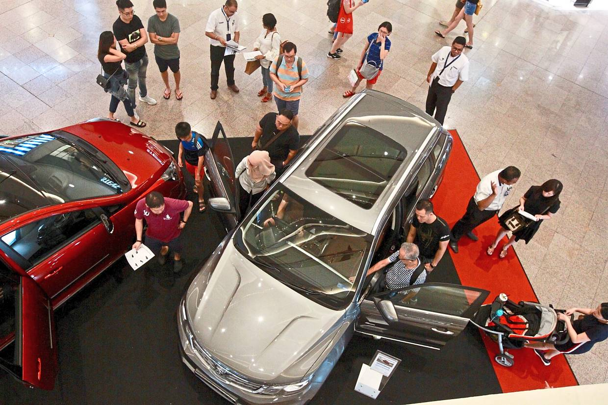 Rising sales: Visitors to a Proton showcase checking out vehicles at a shopping complex in Kuala Lumpur. For the first 11 months of 2019, Proton saw a 51% jump in car sales to 89,000 units.