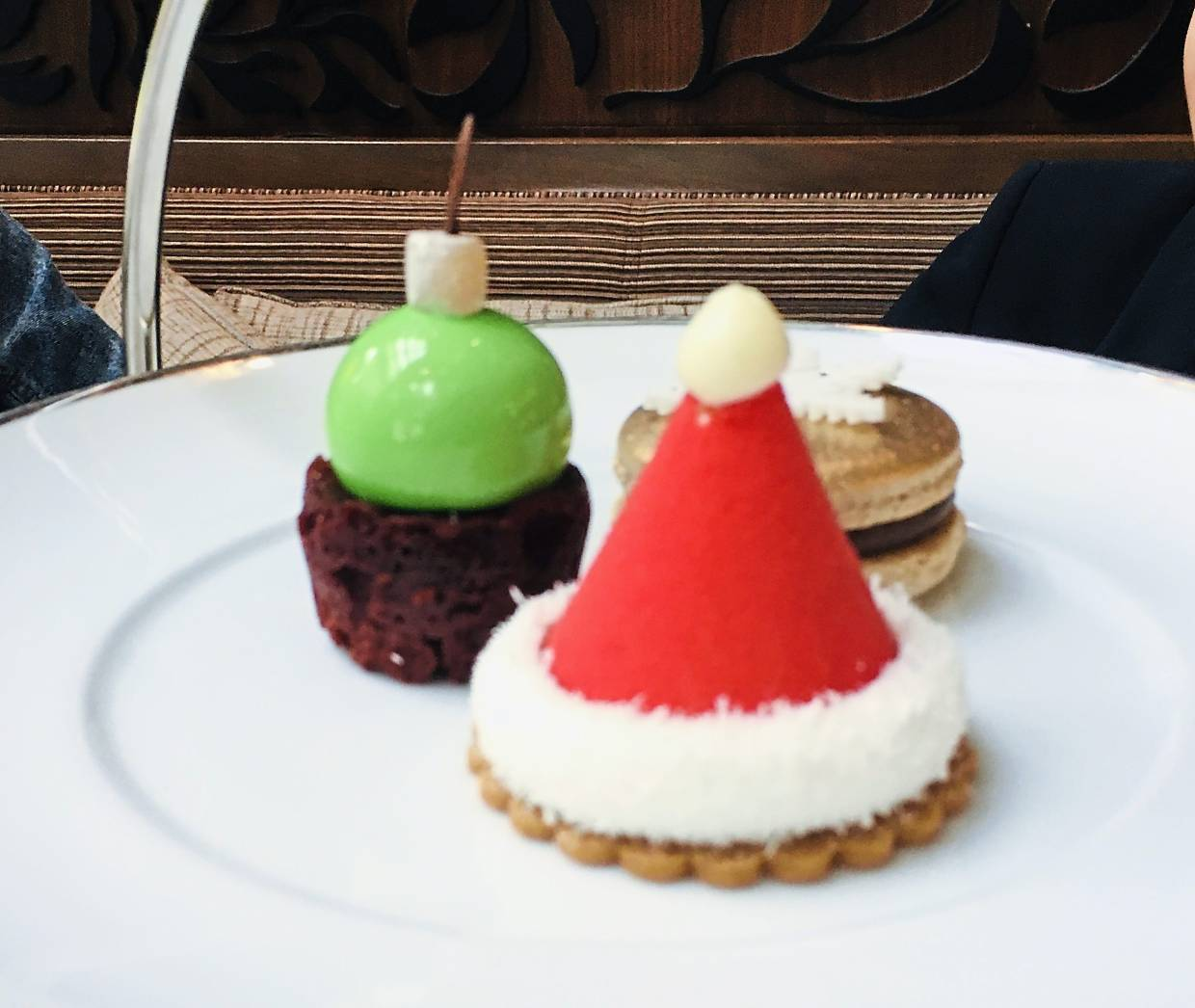 Santa's Hat, Neon Green Red Velvet Bauble and Gingerbread Mandarin Macaron, which are served on the top plate.