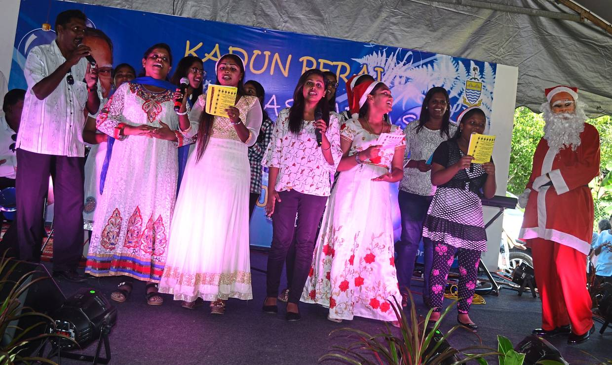 The Nativity Of The Blessed Virgin Mary Church Tamil Choir group singing an evergreen Christmas song. (below )Ramasamy presenting goodie bags to the children. Joining him on stage are (from left) Father Dominic, Satees and David.