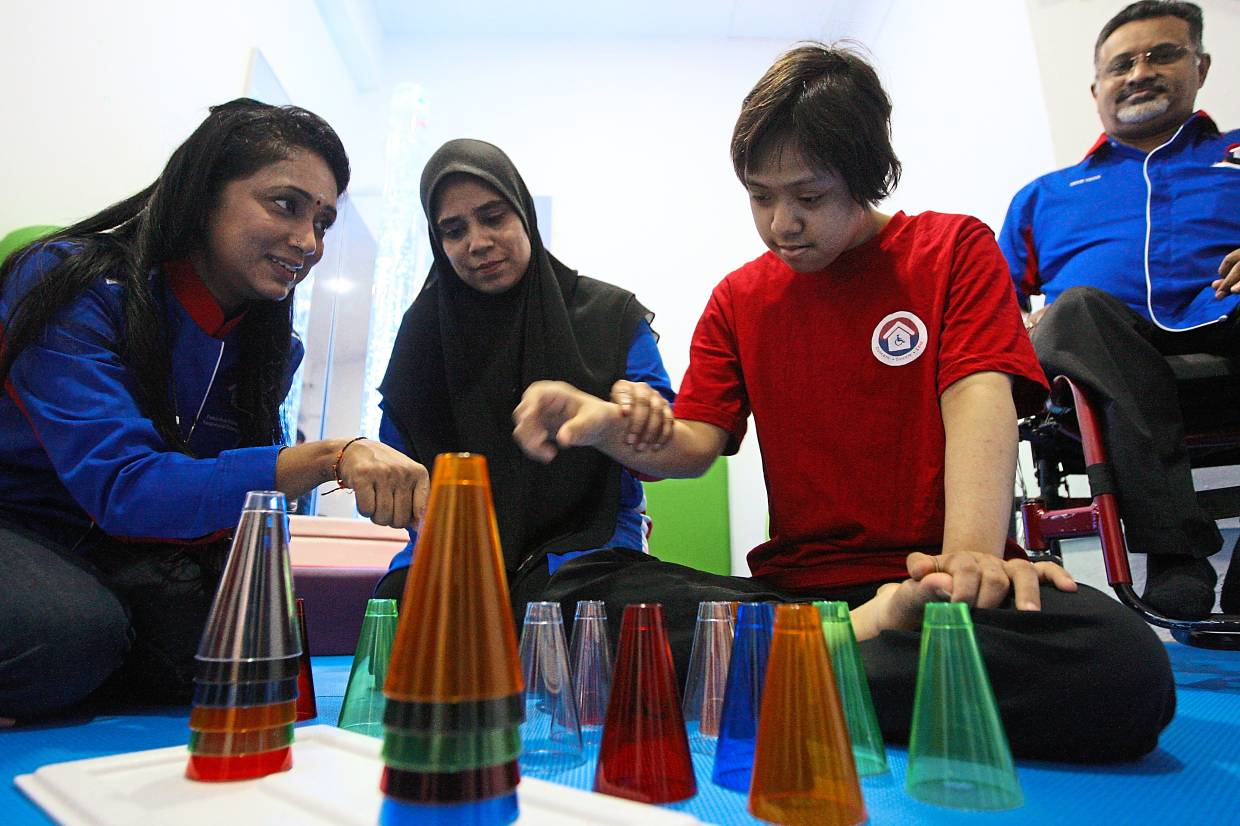 A child with Down Syndrome (right) identifying colors using toys placed inside a  sensory room.