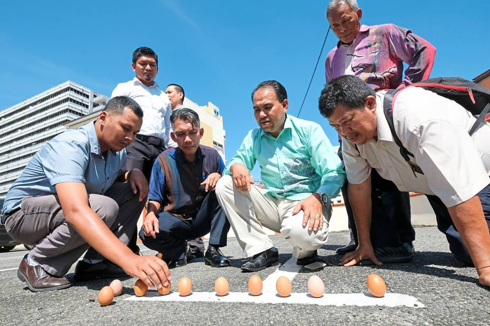 Easy does it: People trying the egg-standing experiment to test the pull of gravity during the annular solar eclipse in Kuala Terengganu. — Bernama