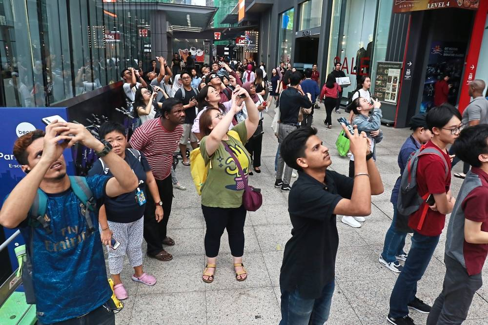 Phone cameras up: Klang Valley folk taking the opportunity to capture the unique occurrence in Kuala Lumpur.