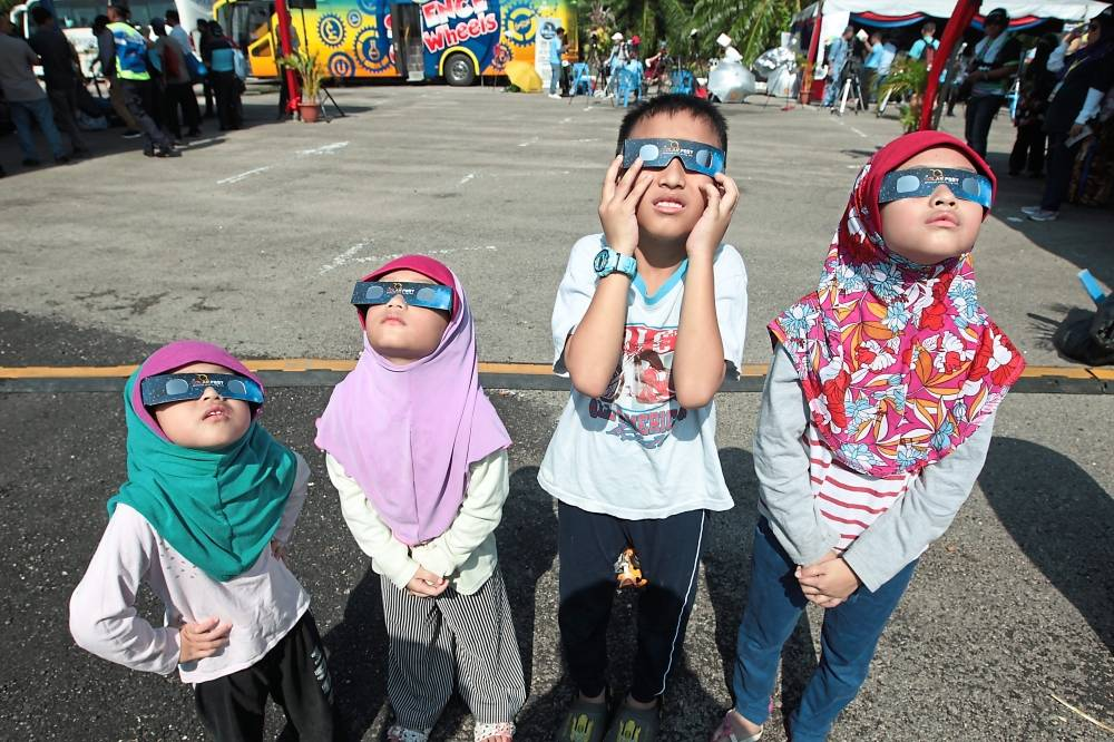 Young enthusiasts: Children using special glasses to view the eclipse at Tanjung Piai, Pontian.