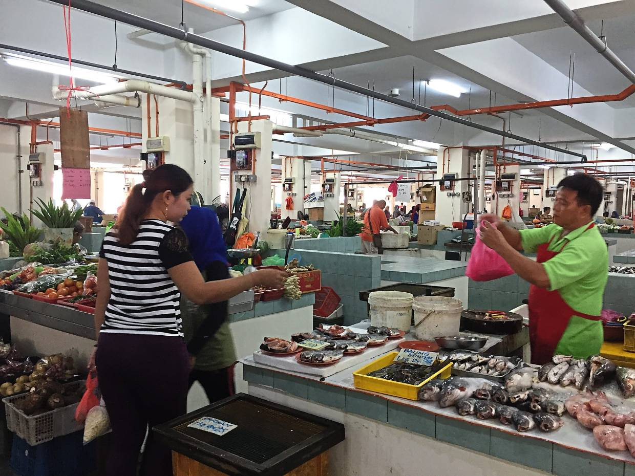 Some of the traders at the Selayang Baru wet market have moved into their allocated lots in the new market. — Filepic