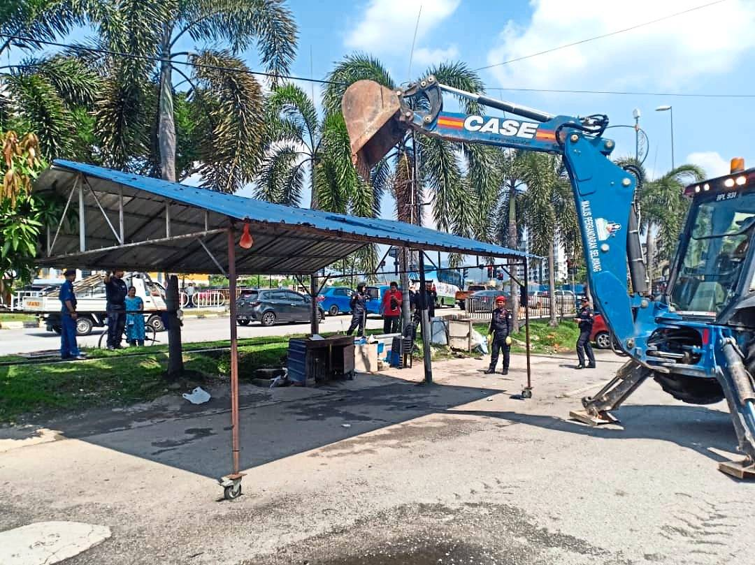 MPS enforcement officers taking down an illegal car wash structure in Kampung Melayu Batu Caves. — Filepic