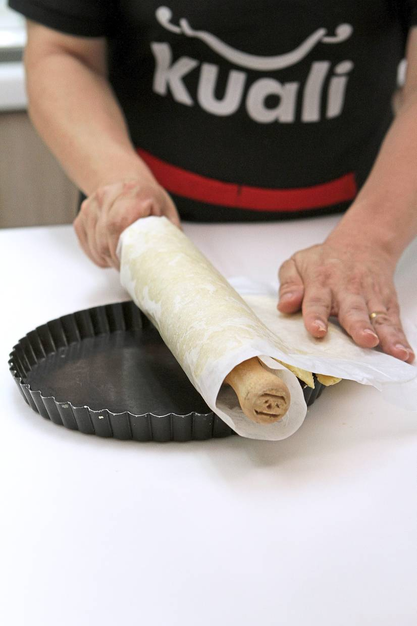 Shortcrust pastry being unrolled onto the baking tin.