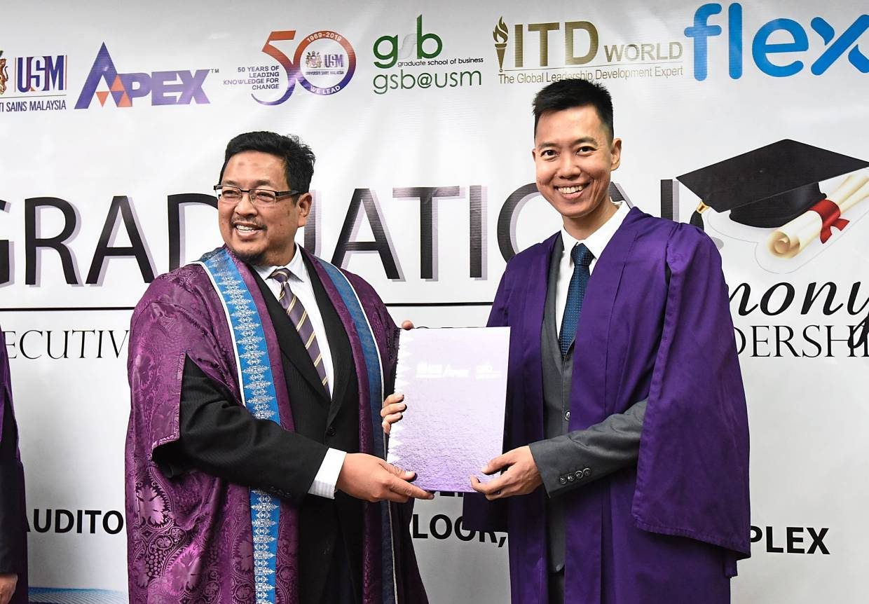 Ho (right) receiving his certificate from Dr Ahmad Farhan.