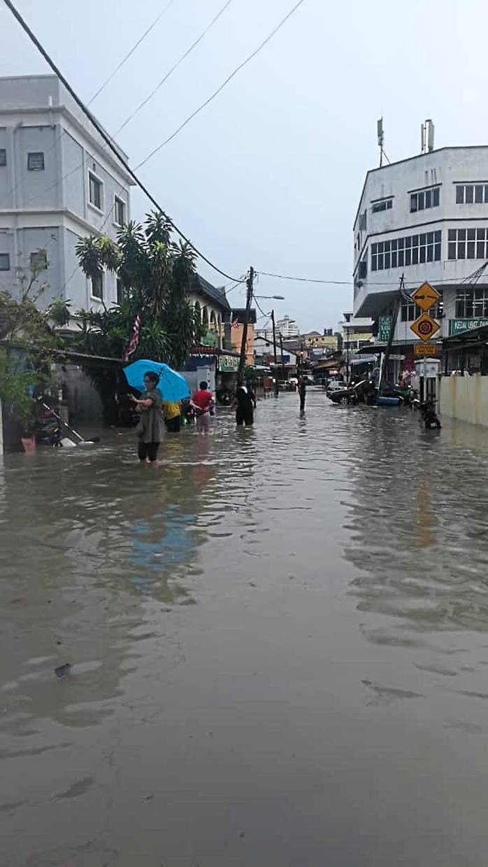 Kampung Cempaka villagers wading through floodwaters to get to higher ground.