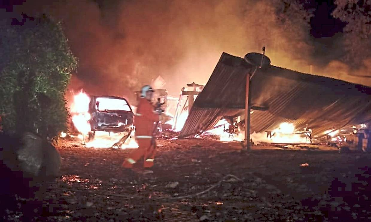 Fatal fire: A firefighter on the scene of the house fire that killed five people in Kampung Menara Pamilaan in Sabah's Tenom district.