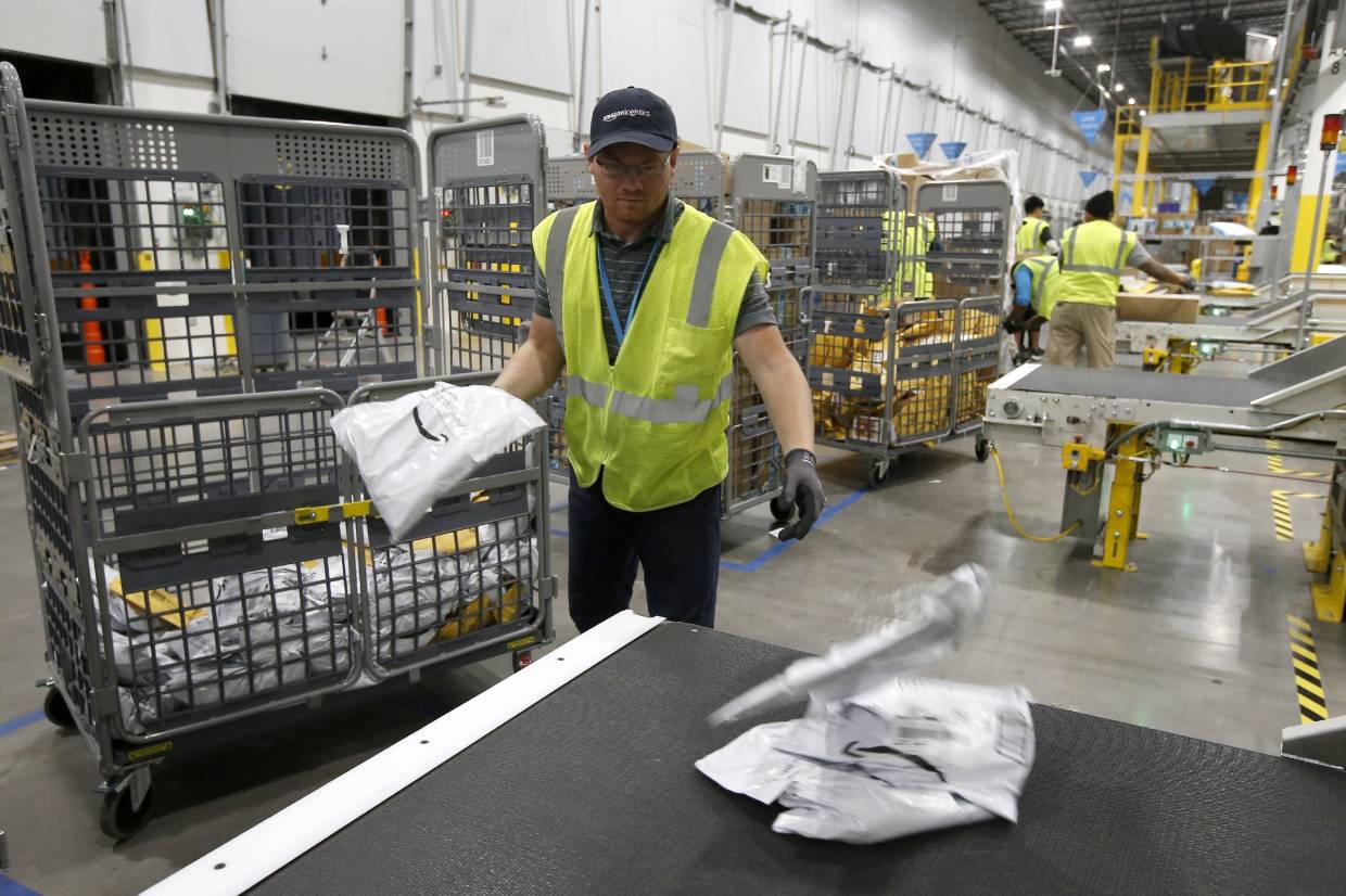 An employee placing packages onto a conveyor prior to Amazon robots transporting packages to chutes that are organised by zip code, at an Amazon warehouse facility in Goodyear, Arizona.