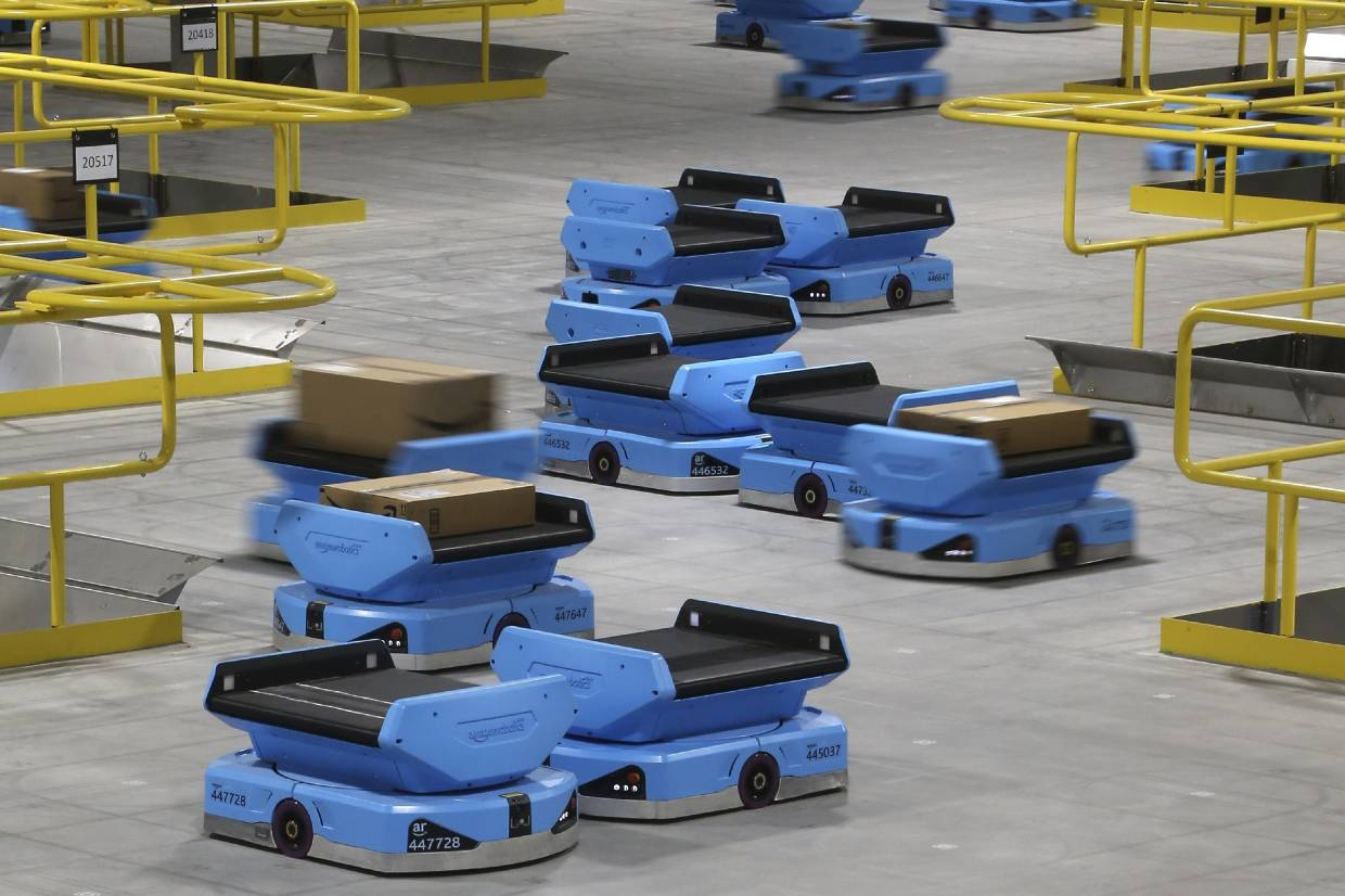 Amazon robots zip along the a warehouse floor, transporting packages from workers to chutes that are organized by zip code, at an Amazon warehouse facility in Goodyear, Arizona.