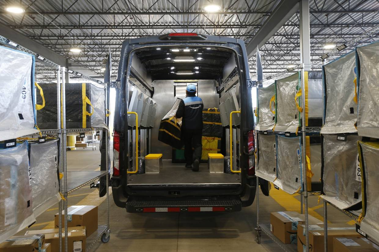 An Amazon delivery driver moves stowed containers into his truck after Amazon robots deliver separated packages by zip code at an Amazon warehouse facility in Goodyear, Arizona.