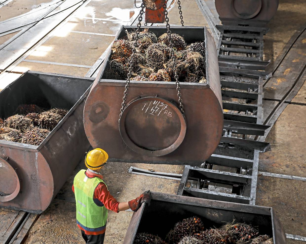 Higher prices: A worker monitors a freight car filled with harvested palm oil fruit bunches being lifted inside a mill of a oil palm estate in Perak. CPO futures closed up RM74 per tonne yesterday. — Bloomberg