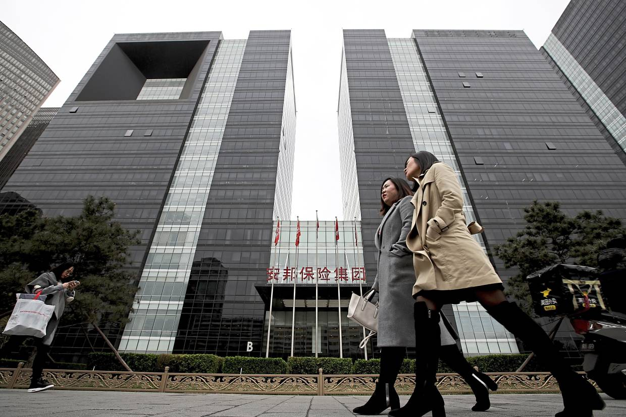 Disposal of stakes: A file picture showing the Anbang Insurance Group office building in Beijing. The group is looking to offload stakes in 12 rural commercial banks. — AP