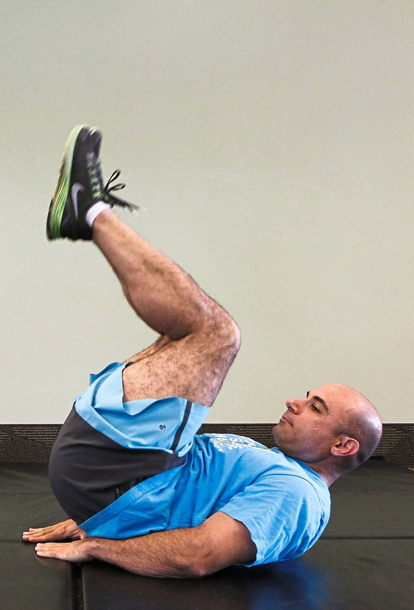 You can pick your own exercises for your HIIT workout, such as the crunches shown here, but make sure they involve most of your major muscle groups. — MCT