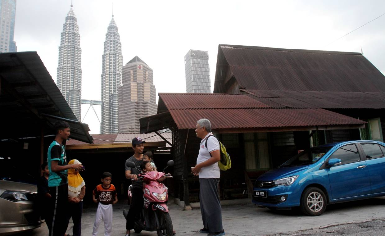 Fuad Fahmy (in white) enjoys showing visitors around Kampung Baru and share stories of his childhood home. -- SHAARI CHEMAT/The Star