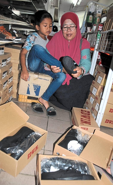 Kazemah helping her nine-year-old son Muhammad Arsyad Danish Alias choose  school shoes at Kedah Shopping Centre.