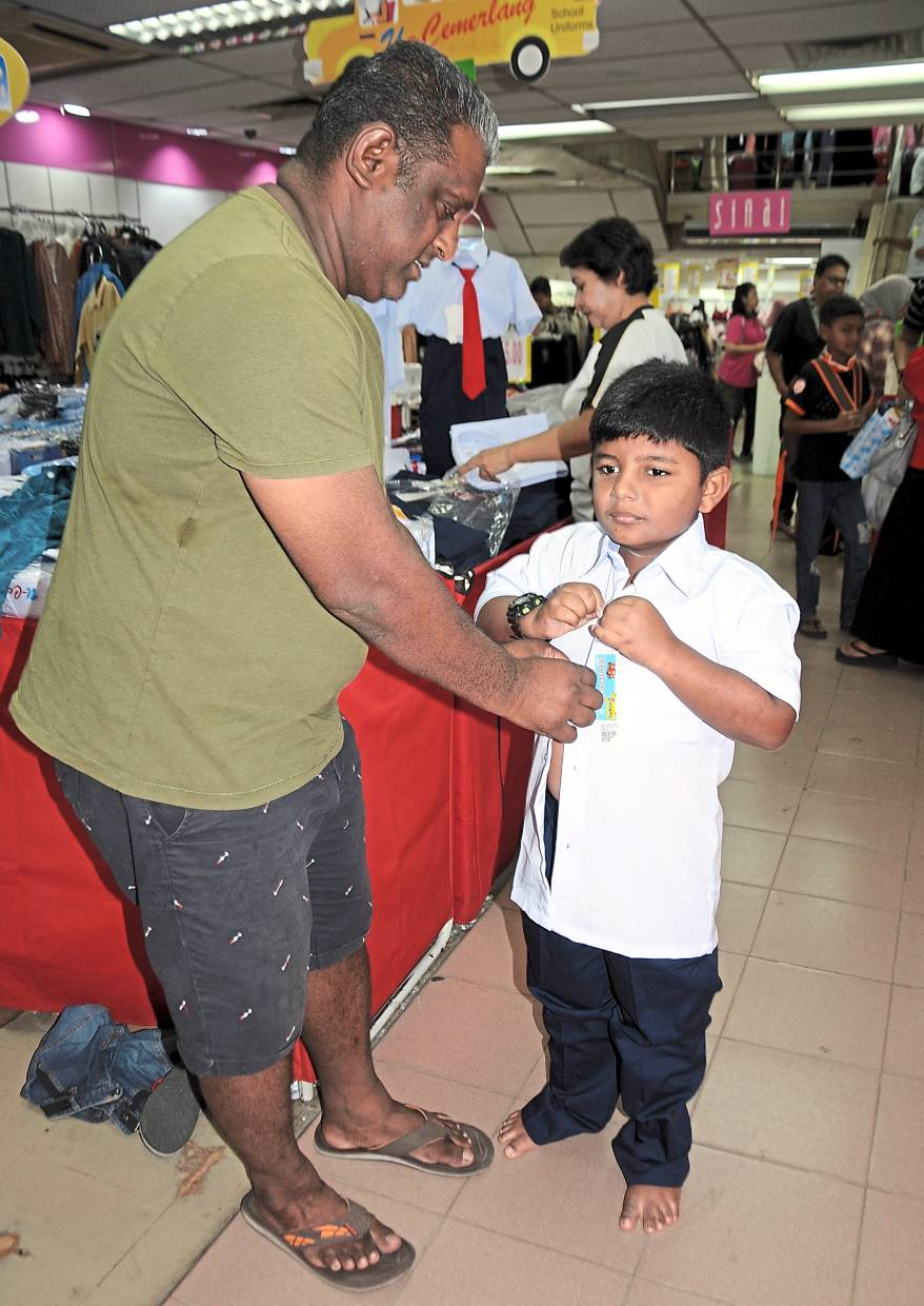 Gajeshan trying on a new uniform with help from father Parthipan.
