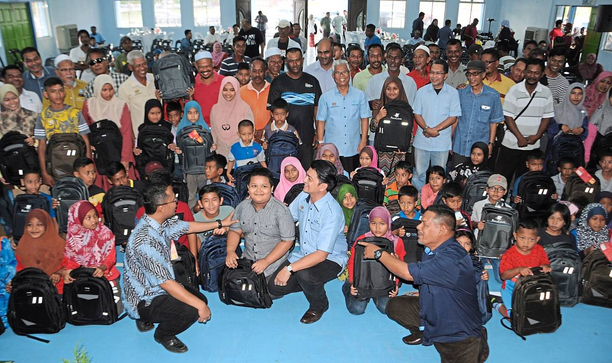 Muhammad Faiz (front, centre) posing with children and parents from the Kuala Kedah Fishermen Association. With them are state youth and sports, tourism, arts  and culture and entrepreneur development committee chairman Mohd Asmirul Anuar Aris (front, left) and National Fisherman's Association of Malaysia chairman Abdul Hamid Bahari (front, right).