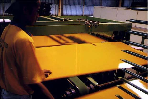 A worker conducting quality control tests at a coated plywood line plant in Sibu.